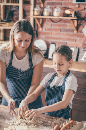 Girl and woman making dough together