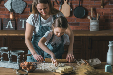 Child and mother rolling knead Stock Photo