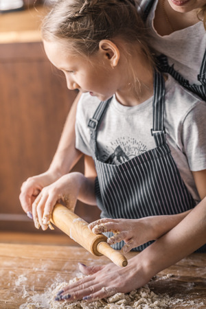 Mother with daughter rolling dough Stock Photo
