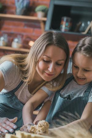 Smiling mother and daughter preparing dough