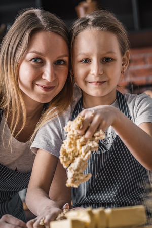 Woman and girl cooking dough Stock Photo