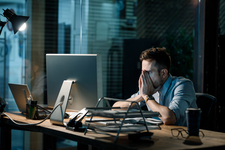 Weary man working in office late Stock Photo