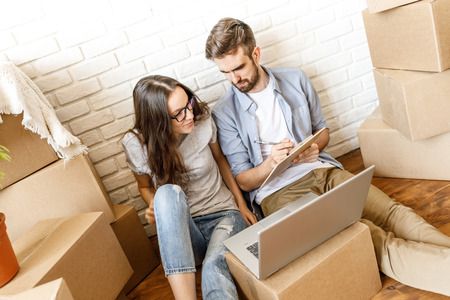 Relaxed couple preparing relocation with clipboard