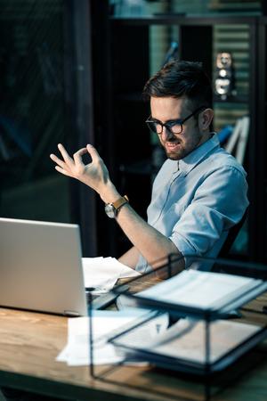 Smiling man gesturing at laptop