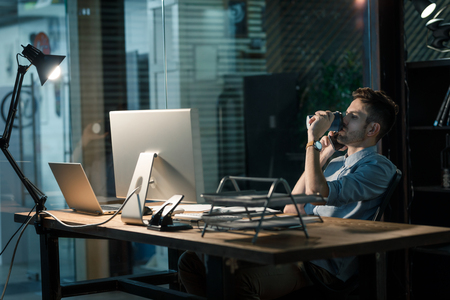 Overworking man with coffee speaking on phone Stock Photo