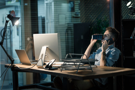 Man overloaded with work having phone call Stock Photo