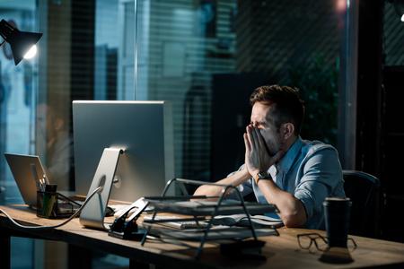 Yawning tired man working overhours Stock Photo