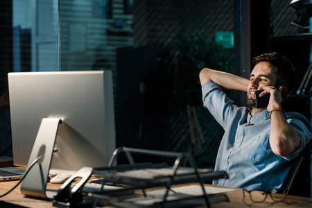 Man chatting via phone in dark office