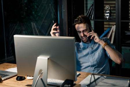 Man chatting on phone at work Stock Photo