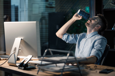 Man drinking coffee working overhours