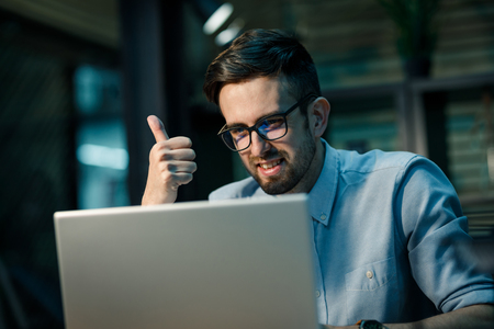 Smiling man speaking via laptop