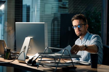 Man working with papers late in office Stock Photo