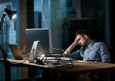Exhausted worker watching computer Stock Photo
