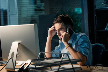 Frowning man working late with computer Stock Photo