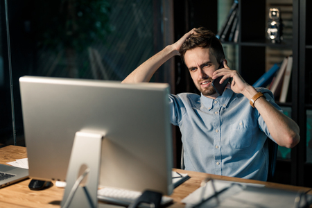 Man having phone call late in office Stock Photo
