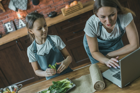 Mother and girl using laptop on kitchen