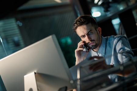 Frowning man having overtime job