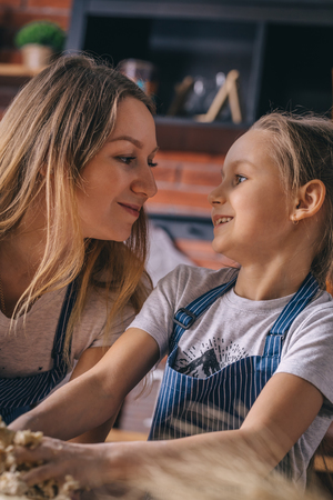 Happy little girl and mother cooking knead