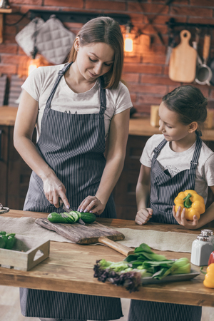 Mother and daughter cooking vegetables