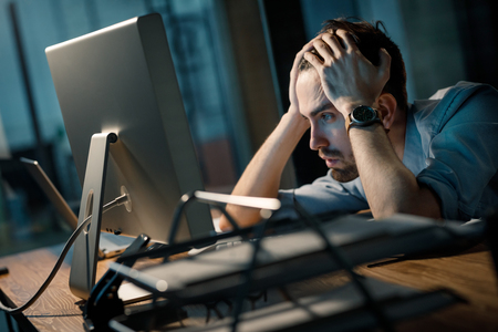 Exhausted man watching computer in evening