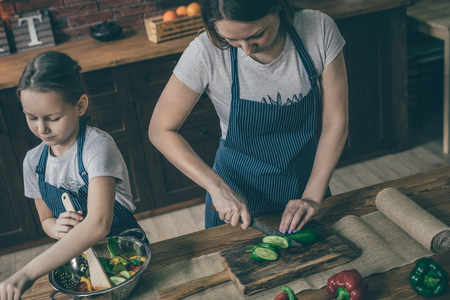 Mother and daughter cutting and mixing salad
