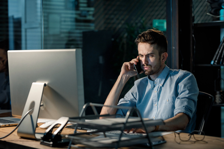 Overloaded worker speaking on phone in office Stock Photo