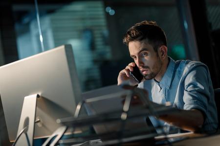 Man on phone working overhours Stock Photo