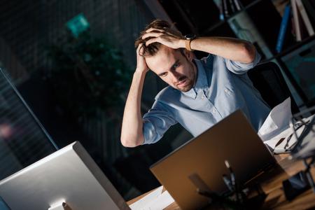 Stressed man watching laptop in despair