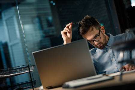 Thoughtful man using laptop in office