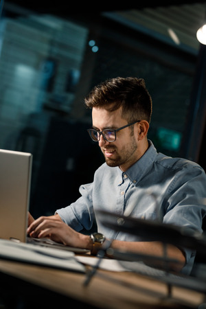 Smiling man using laptop in office Stock Photo