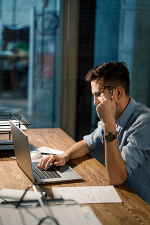 Confident man working with laptop