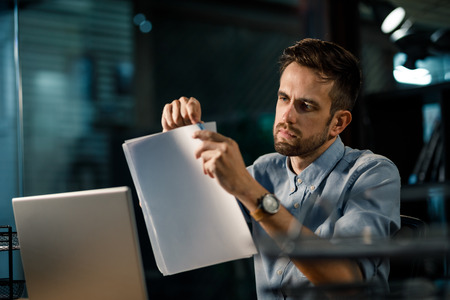 Concentrated man stapling papers Stock Photo