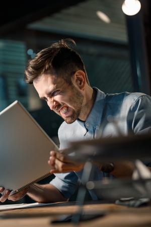Furious man yelling at computer