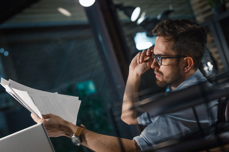 Employee in glasses working with papers