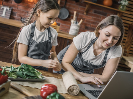 Mother and daughter at laptop on kitchen Stock Photo