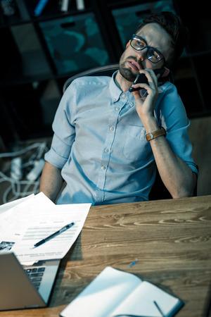 Tired man speaking on phone