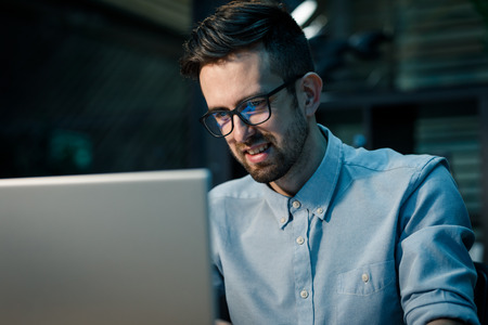Content man in glasses using laptop Stock Photo