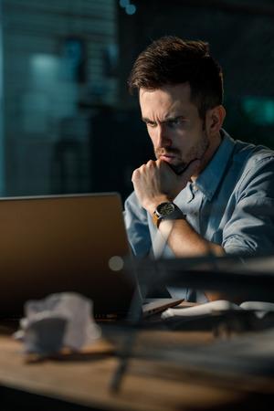 Serious man using laptop at work