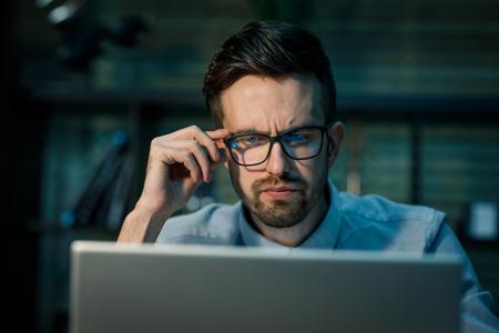 Pensive man working on laptop