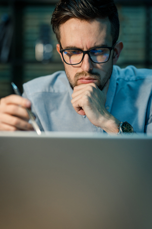 Concentrating worker using laptop Stock Photo