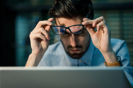 Young man in glasses focusing on laptop Stock Photo