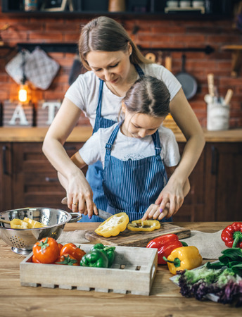 Mother helping daughter with pepper cut