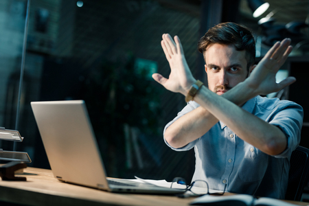 Stressed office working doing stop gesture