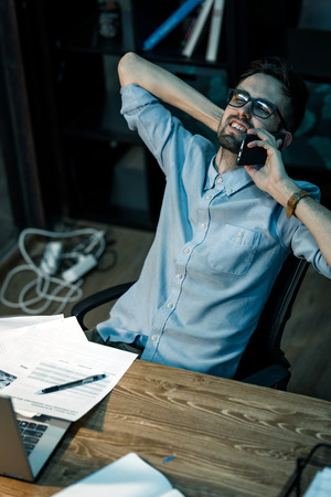 Relaxed man speaking on phone at desk Stock Photo