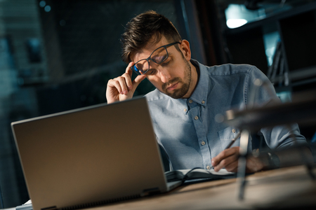 Smart man writing at working table