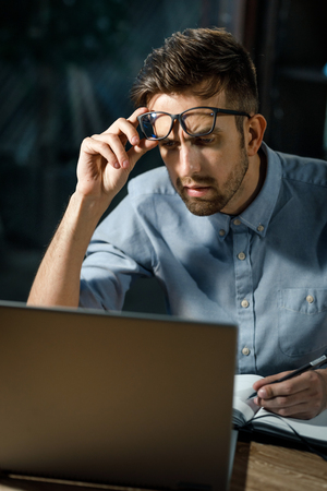 Pensive man watching laptop and working Stock fotó - 103154760