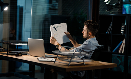 Worker looking through papers Stock Photo