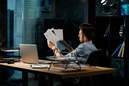 Homme occasionnel lisant des papiers au bureau