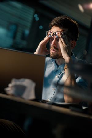 Sleepy worker using laptop