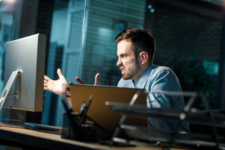 Angry man with computer in office Stock Photo
